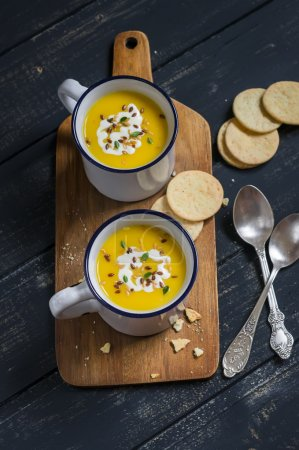 Photo for Pumpkin soup in ceramic mugs on a wooden surface - healthy food - Royalty Free Image