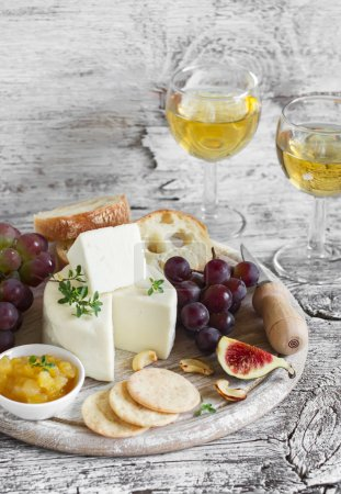 Photo for Delicious appetizer to wine - ham, cheese, grapes, crackers, figs, nuts, jam, served on a light wooden board, and two glasses with white wine on bright wooden surface - Royalty Free Image