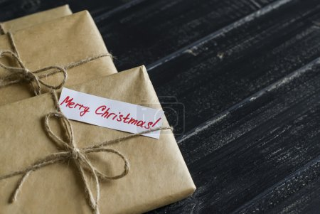 Homemade Christmas gifts in kraft paper on a dark wooden surface. Free space for text.