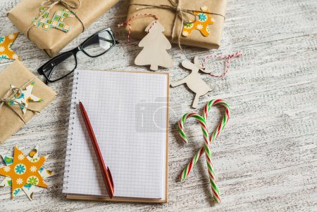 Christmas gifts, Christmas ornaments, candy and an open blank notebook