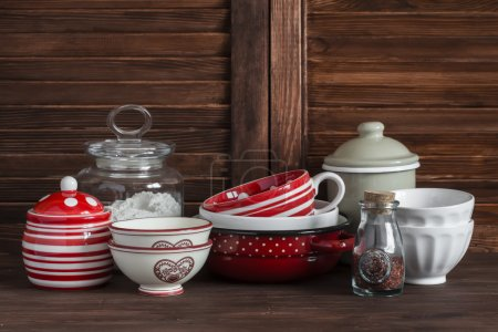Kitchen still life. Vintage crockery - jar of flour, ceramic bowls, pan, enamelled  jar,  gravy boat. On a dark brown wooden table. Vintage and rustic style