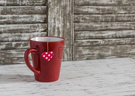 Photo pour Tasse de thé avec un sachet de thé fait maison avec des cœurs en papier sur un fond rustique en bois clair. encore aujourd'hui la vie de la Saint-Valentin - image libre de droit