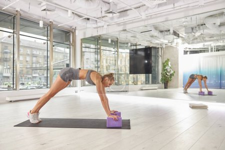Beautiful caucasian slim woman is doing stretching...