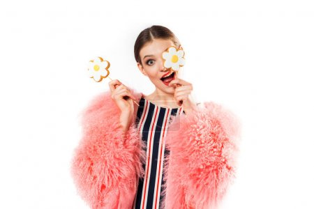 Mädchen mit Süßigkeiten auf Weiß im rosa Pelzmantel. Hübsche Frau mit Make-up posiert attraktiv mit Lutscher am Stock im Studio. Süßigkeiten wie Kamille, Blume in der Hand.Freudig lachende Dame auf der Party