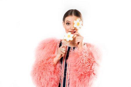 Modisches Mädchen mit Süßigkeiten auf Weiß im rosa Pelzmantel. Make-up attraktiv posiert mit Lutscher in studio.candy Kamille, Blume in der Hand.Versteckt ohne Gesicht .Joyful lachende Dame auf der Party.