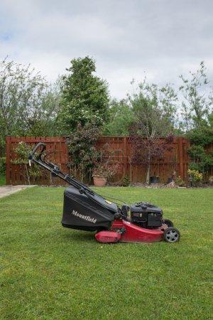 Cramlington, Northumberland, UK 25 MAY 2015. Lawn mower in garden
