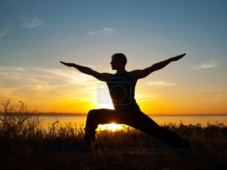 Man in yoga warrior pose standing  outdoors