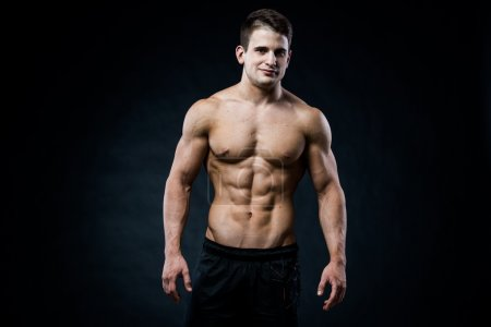 Muscular male model bodybuilder looking straight to the camera. Isolated on black.