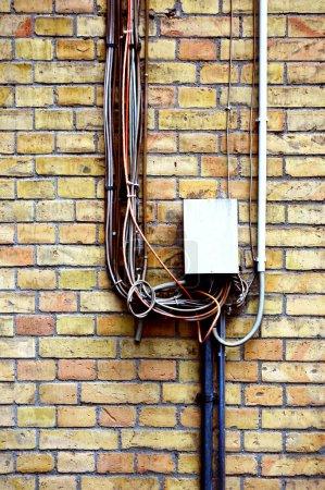 Photo pour Mur en brique classique avec câbles, fils, boîte à fusibles sur joints clairement visibles et texture comme fond de gabarit - image libre de droit