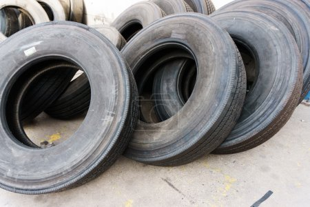 Tires stacked on cement ground, used tires