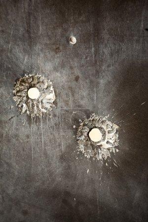 Bullet holes in metal surface