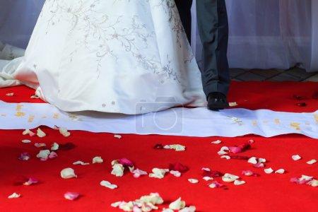 Photo pour Félicitation de sa femme pour le mariage. Invités de mariage griller la mariée heureuse. Concentration sélective sur le sol avec des pétales de rose. Moments de cérémonie de mariage - image libre de droit