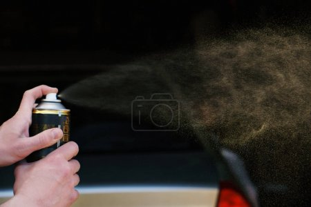 A man sprays paint from a can in front of a car. H...