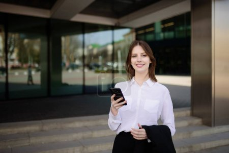 Joven hermosa chica sonriente responde a un mensaje en su teléfono móvil