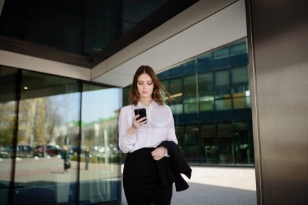 Joven hermosa chica responde a un mensaje en su teléfono móvil