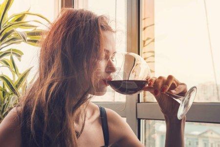 Retrato de primer plano de una joven cliente bebiendo vino tinto con los ojos cerrados. Mujer bebiendo vino, tomando un SIP de un vaso de vidrio. Degustación de vinos en el restaurante.