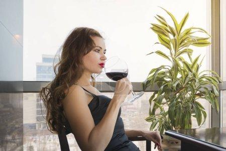 Una joven hermosa con un vestido negro se sienta en un restaurante y bebe vino de una copa. primer plano de la joven mujer que su mano sosteniendo con vino tinto de cristal como un mirando hacia fuera en la ventana.