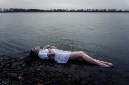 Photo for Girl lying on the rock of dark river . Ophelia conceptual - Royalty Free Image