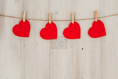 Red heart hanging on the clothesline. On old wood background