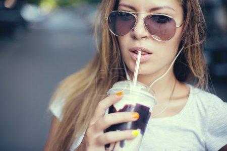 pretty girl with milk shake listening music on the street. Sunset.