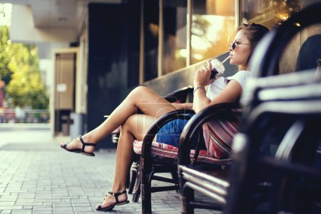 Photo for Outdoor closeup portrait of pretty stylish fashion girl having fun drinking chocolate milkshake in a cafe outdoors - Royalty Free Image