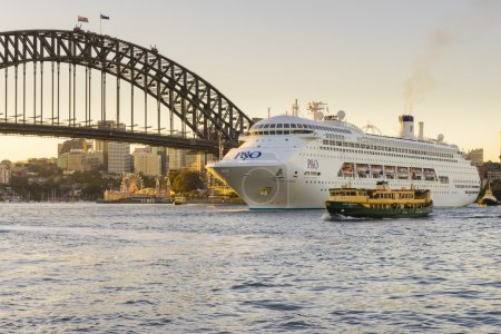 Luxury cruise ship near Sydney Harbour Bridge at sunset