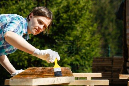 Femme en appliquant de la peinture de traitement du bois frais