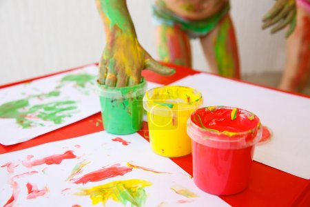 Child dipping fingers in non-toxic finger paints