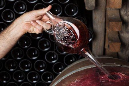 Photo pour Sommelier vin rouge fût de chêne, l'échantillonnage bouteilles en arrière-plan - image libre de droit