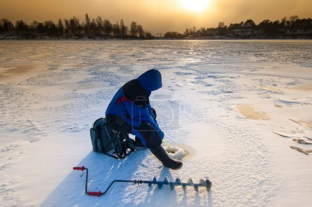 Photo pour Pêche sur glace sur la glace épaisse avec la tarière de glace de main devant - image libre de droit