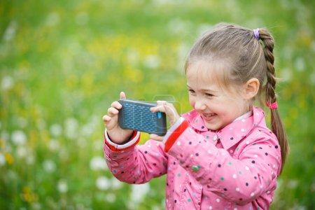 Foto de Pequeña niña sonriente y curiosa fotografiando con su teléfono inteligente, explorando la naturaleza y de pie en un prado de diente de León. Estilo de vida activo, curiosidad, perseguir un hobby, tecnología y concepto de niños. - Imagen libre de derechos
