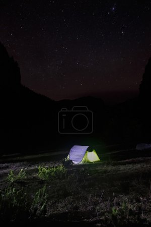 Night landscape with tent pitched on a mountain pasture