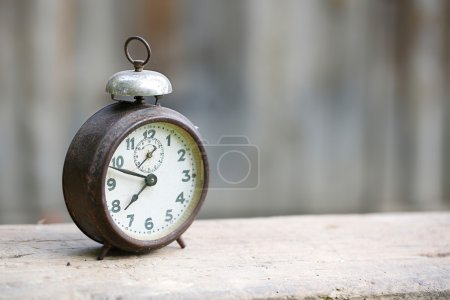Photo for Vintage metal analog alarm clock with Arabic numbers and windup mechanism, sitting on a wooden bench with retro background. Time is now, time is money, old times concept. - Royalty Free Image