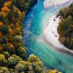 Pristine alpine turquoise river meandering through...