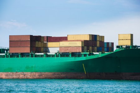 Photo for Hull of a big container ship docked in port, loaded with various colorful containers prepared for transportation. Global transportation, global business, consumerism concept and background. - Royalty Free Image