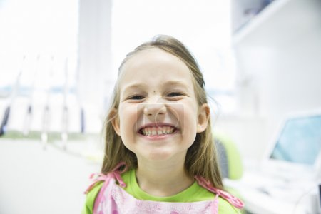 Photo for Relaxed little girl showing her healthy milk teeth at dental office, smiling and waiting for a checkup. Early prevention, paedodontics and no fear concept. - Royalty Free Image