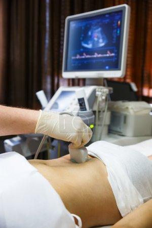 Doctor doing an ultrasound on a patient abdomen