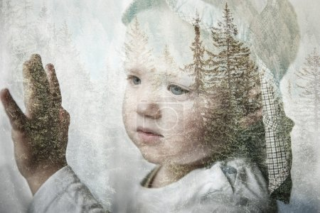 Little boy daydreaming, looking out the window, double exposure