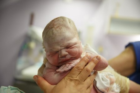 Midwife holding up a vernix covered newborn just a...