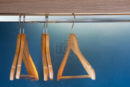 Photo for Close up of wooden hangers inside a blue closet with selective focus on the stainless pin. - Royalty Free Image