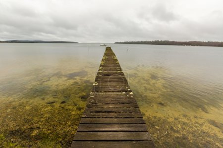 Photo for Mystic cloudy landscape and wooden jetty in Georges Bay, St Helens, the most important city on the East Coast, Tasmania, Australia. Concept of simplicity, purpose, direction and infinity. - Royalty Free Image