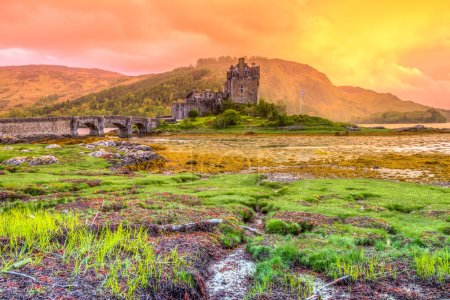 Photo for Eilean Donan Castle at sunset, Dornie, Kyle of Lochalsh in Scotland, United Kingdom. It is the most visited castle, situated on an island at the confluence of three sea lochs. - Royalty Free Image