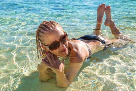 Attractive woman sunbathing in tropical water