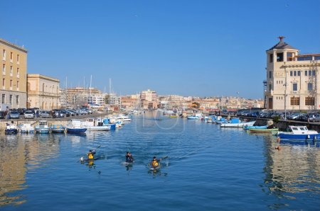 Fishing boats and kayakers in the darsena of Ortigia Islet from the Bridge Umbertino. On the background the skyline of Siracusa on the mainland
