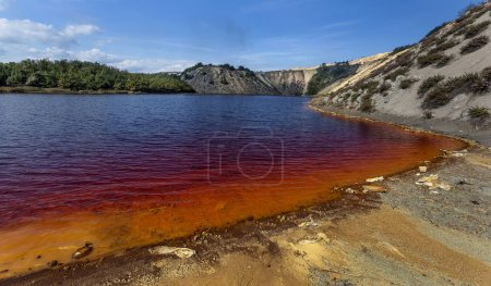 Red artificial lake and hills as a result of minin...