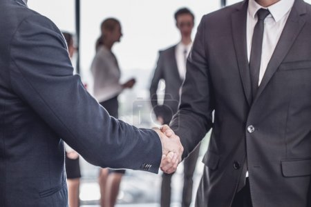 Photo for Handshake in front of business people team in office - Royalty Free Image