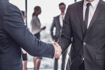 Photo pour Poignée de main en face de l'équipe de personnes d'affaires au bureau - image libre de droit