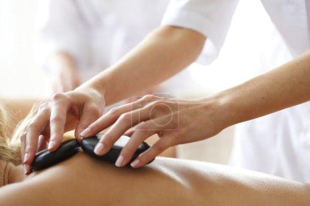 Photo pour Jeune belle femme au spa se faire masser la pierre chaude - image libre de droit