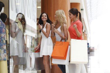 Photo pour Jeunes belles femmes heureuses avec des sacs à provisions dans le centre commercial - image libre de droit