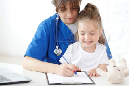 Photo for Nurse and kid writing medical record - Royalty Free Image